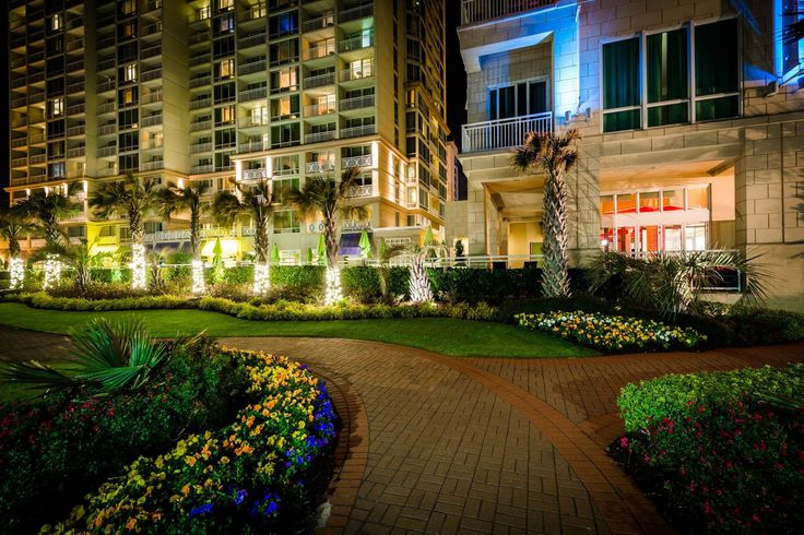 Gardens along a walkway and highrise hotels at night, in Virginia Beach, Virginia.