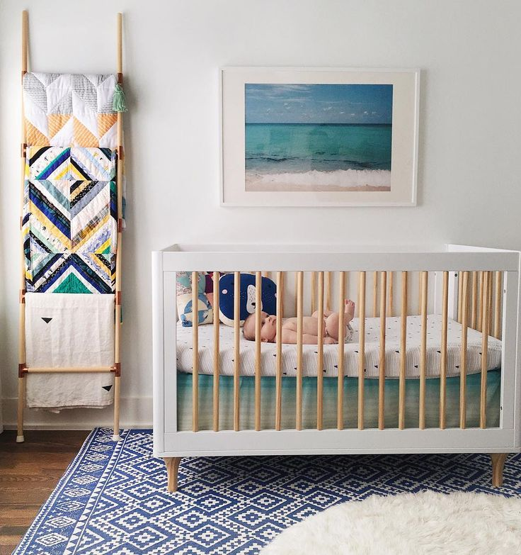 Modern Nursery Ideas With Peach And Turquoise Accents A Blanket Ladder To Add Color Check Out The Blue Patterned Area Rug White Natural Wood