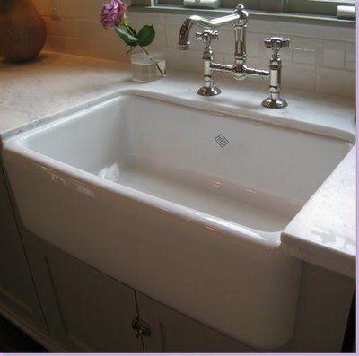 White ceramic farm sink, white quartz counters, white cabinets with vintage clasps...