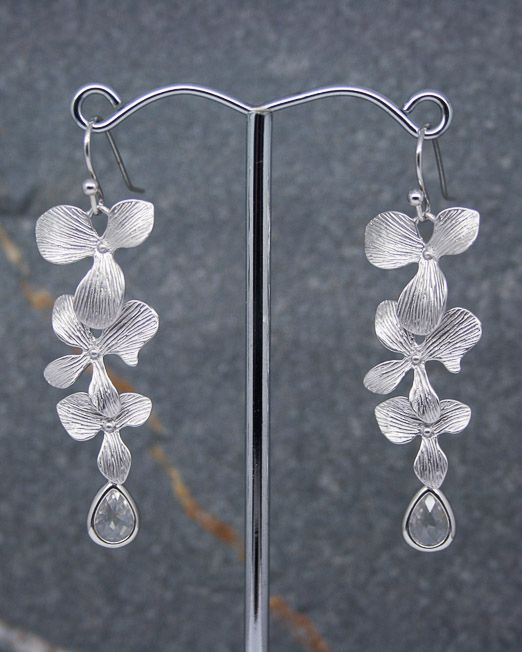 An elegant pair of cascading orchid earrings makes for a perfect gift for any occasion.  The three flowers move independently from each other to create a beautiful light catching effect. Overall length is 50mm from the top of the hook.  The glass crystal drop measures 7 x 11mm in rhodium plated over brass settings.  All flowers have been created in brass and matte rhodium plated.   All of our jewellery comes in blue or silver box with ribbon bow.  #Crystal #Earrings #Floral #Portside