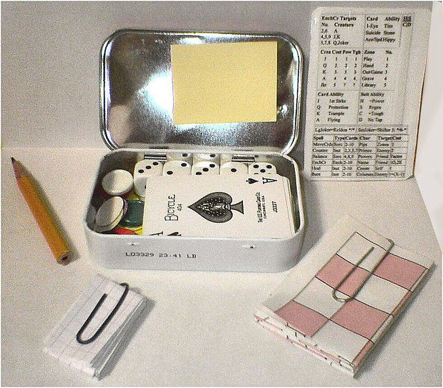The Altoids Pocket Games Chest contains a half-dozen colorful plastic markers, sixteen cardboard 'winks', a folding gameboard, some grid paper, a pencil, five dice, a deck of 'mini' playing cards, a pad of Post-it notes, and a laminated cheatsheet for some favorite games.