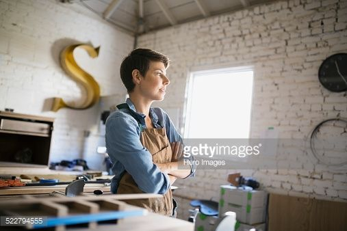 Stock Photo : Pensive female carpenter with arms crossed in workshop