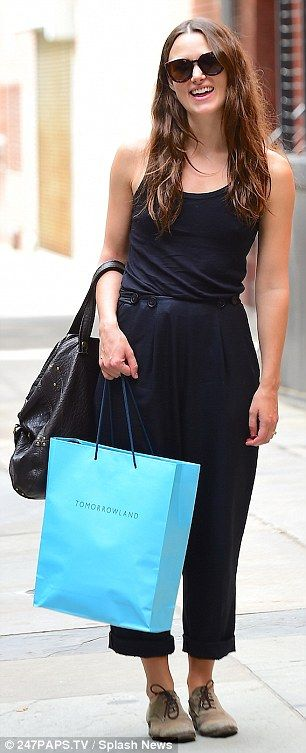 Shopping up a storm: Keira looked gleeful as she strolled the streets wearing the oversize...