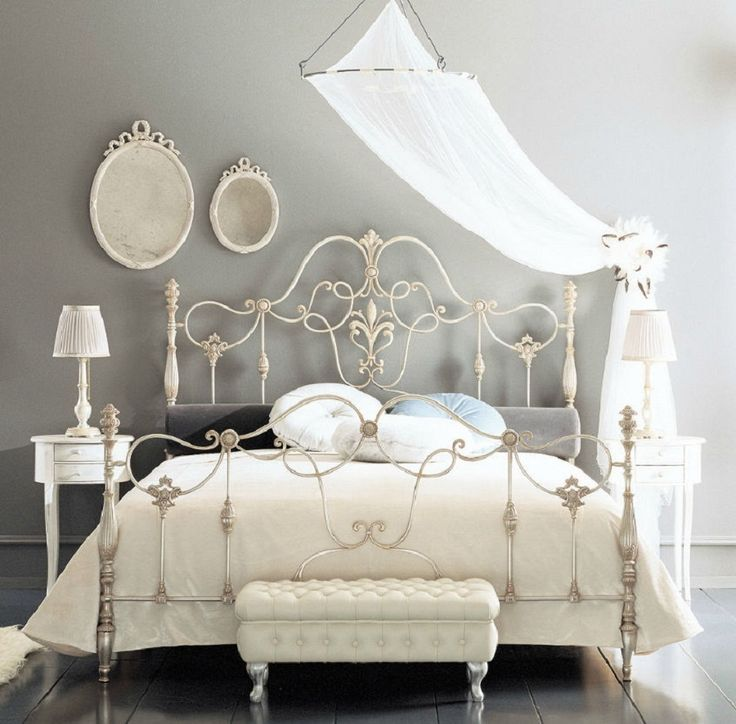 Fancy Wrought Rod Iron Beds Curved With Silver Color And Wall Mounted Mirror Also Small White Table Lamp Stained Atique Furniture