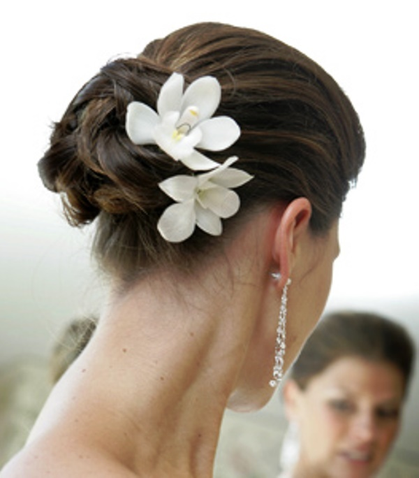 Bride's looped bun white flowers wedding hairstyle