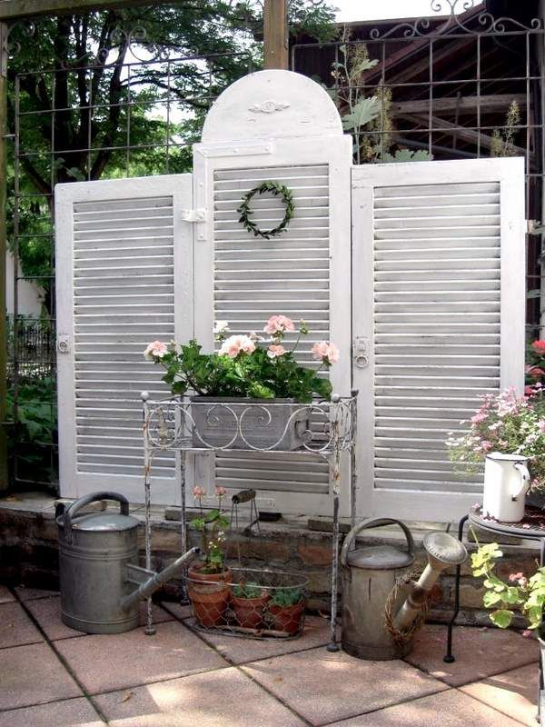 White shutters used as privacy fencing For the back yard and garden.