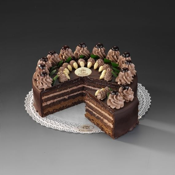 Tort Czekoladowy Czekoladowy biszkopt upieczony z dodatkiem orzechów laskowych. W torcie dominuje puszysty krem czekoladowy z odrobiną alkoholu. Warstwa grylażowego kremu to kompozycja czekolady, orzecha laskowego i krokantu. Ozdobiony czekoladą, migdałami i wiśniami z syropu.