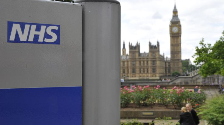 A National Health Service (NHS) sign is seen in the grounds of St Thomas' Hospital, in front of the Houses of Parliament in London June 7, 2011. Reforms to Britain's cherished state-funded health service will not result in a U.S.-style private system, Prime Minister David Cameron said on Tuesday, seeking to win over wary Britons.