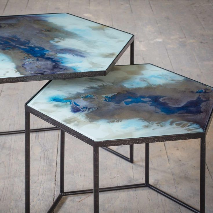 Splashing dynamic swirls of deep blue on the table's silky surface and allowing it to form a life of its own, the Organic tables are crafted using an exceptional method of layering pigments and metallic inks. The handcrafted nature imparts uniqueness to the tables—no two pieces are precisely alike—and the two matching pieces see the fluid movement of deep blue unbroken despite its separation. Vivid and seemingly alive, the Organic tables perfectly capture the movement within two frames.