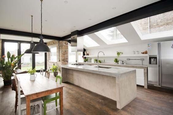 The angled glass ceiling over the kitchen adds light, views and extra dimension to this kitchen and casual living space without taking valuable wall space. I don't like the heavy black beam but do like concrete island and section of face brick wall at the end warms it up and could have a fireplace in it.