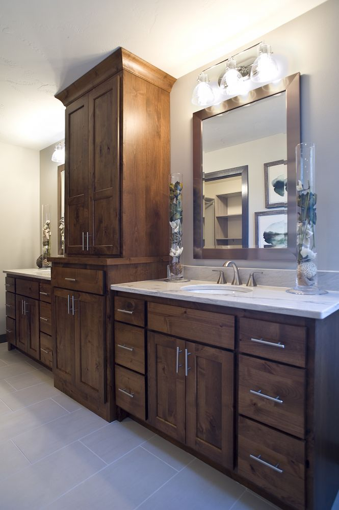 Knotty alder vanity with a large linen tower, dual sinks and white quartz countertops.