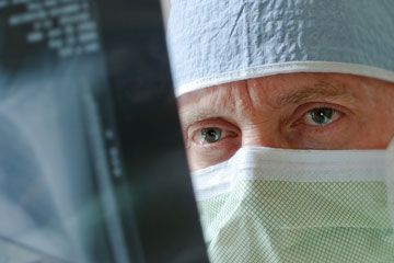 a physician wears a mask while viewing x-ray results