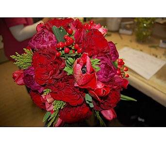 Hand tied bouquet of red berries, anemones, heart garden roses, tulips, peony and touches of fresh cedar greens.