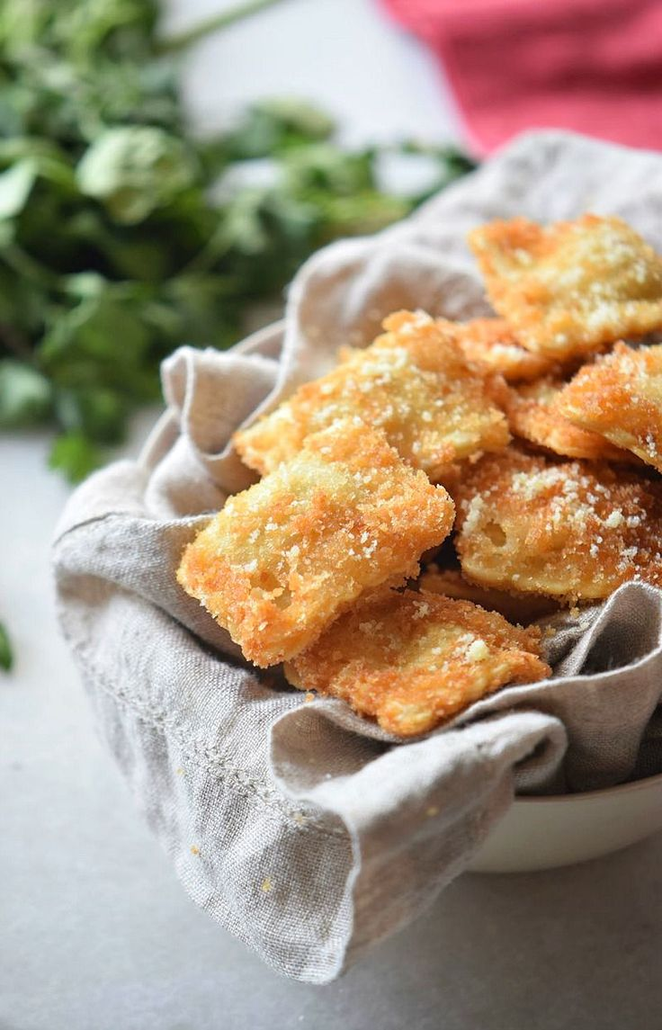 Oven toasted ravioli appetizer recipe with a Parmesan crust - if you're looking for a crowd pleasing appetizer recipe, this is the one! We love these crispy ravioli bites, baked, not fried