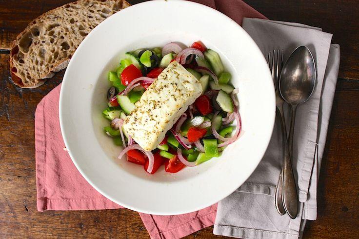 Griekse salade met gebakken feta. Ingrediënten: • 2 tomaten • ½ komkommer • ½ groene paprika • 1 kleine rode ui • 3 el Kalamata (zwarte) olijven • 2 plakken feta van elk ± 50 gram • 1 tl gedroogde oregano • 3 el olijfolie • 1 ½  el rode wijnazijn • peper/zeezout