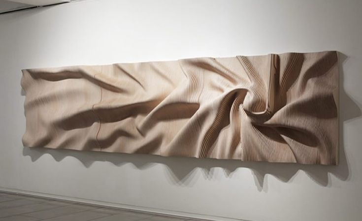 Wood disguised as scrunched fabric  See others:  http://illusion.scene360.com/art/18973/wood-in-motion/