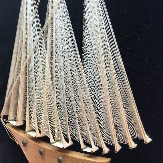 Intricate nail and string art wall hanging. Sailboat with carved wooden base and brass accents on black velvet backing. Good vintage condition. All string is taught and in tact.  Dimensions- 14.75 high x 11.50 wide