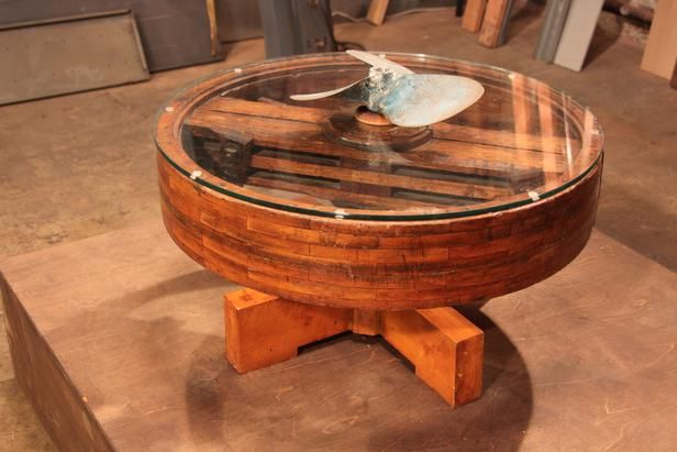 45 Unbelievable Flea Market Flips: After adding a glass top and connecting the boat propellers, this industrial pulley makes for one amazing coffee table.  From DIYnetwork.com