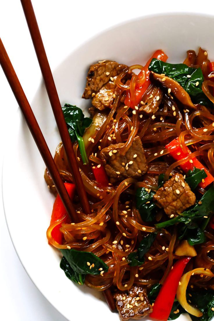 Japchae, this easy Korean noodle stir-fry recipe, is quick and easy to make, it's full of veggies (red peppers, carrots, onions, mushrooms, spinach), and tossed in the most delicious sesame-soy-maple sauce. Feel free to make yours with steak, chicken, pork, shrimp, or tofu. Or just keep it vegan with veggies only. | Gimme Some Oven #stirfry #korean #japchae #dinnerrecipes #glutenfree