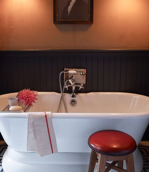 Wallpaper With a Twist  In this bathroom, a Sunrise Specialty tub sits in front of the beadboard painted with Benjamin Moore's black. The portrait of George Washington is a flea-market find.  Bright Idea: A coat of varnish gives inexpensive Kraft paper new life as moody (and durable) wallpaper.