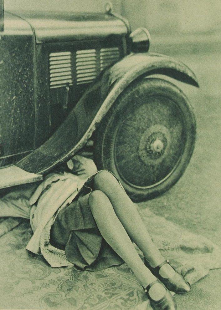 Girl checks for repairing her car, ca. 1920s