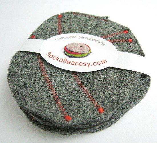 Modern tableware: Wool felt coaster set.  Puzzled together from offcuts of thick industrial wool felt and sewn with contrasting bright orange thread.