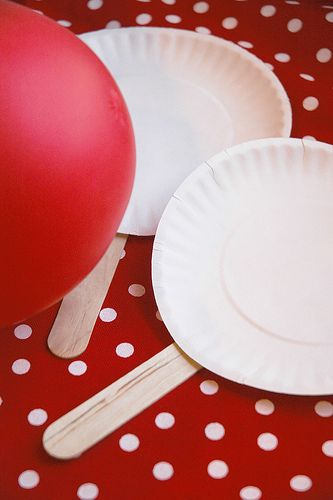 paddle ball with a red balloon and paper plates paddles