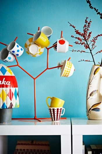 A collection of colourful cups on the branches of a mug tree