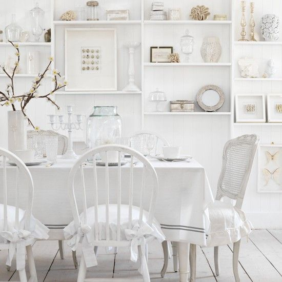 This country-style decorating idea treads the line between austerity and opulence - wooden chairs with ornate detail are teamed with plain linens with flounced cushions and earthy stoneware for fresh and airy country feel.