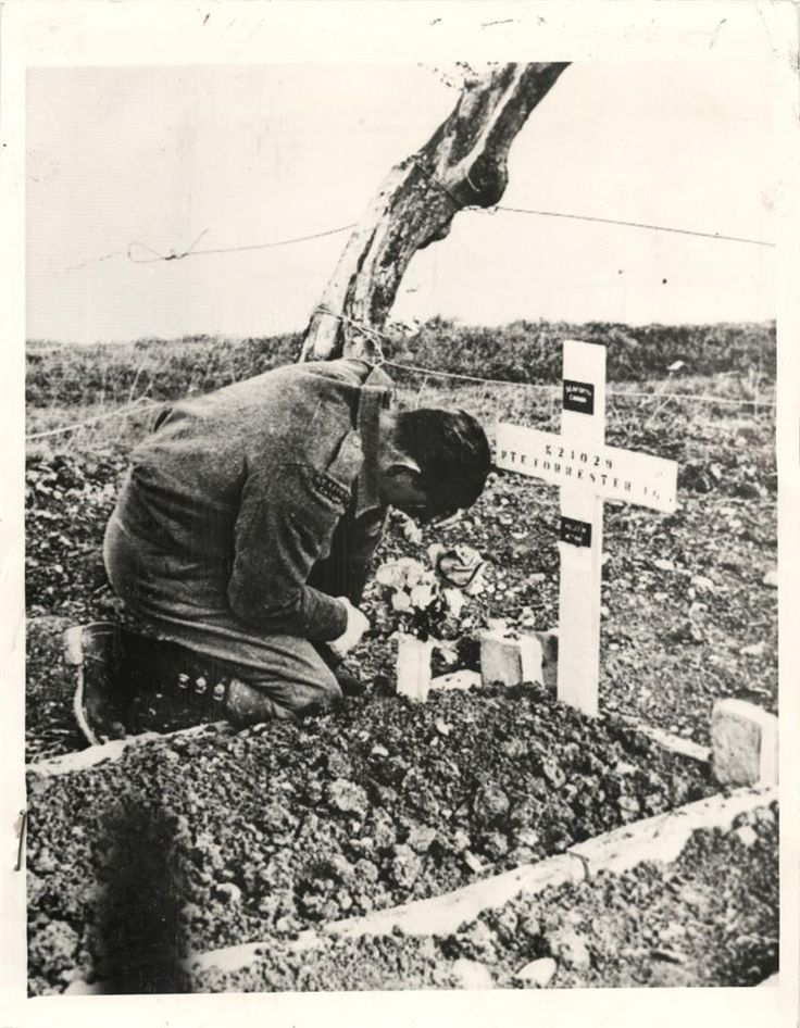 1944- Pvt. Ralph Forrester of the Canadian Seaforth Highlanders prays at his brother's grave in an Italian cemetery where members of the battalion are buried.