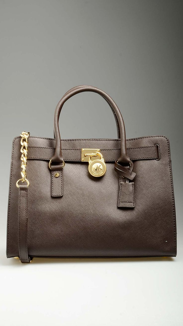 Dark chocolate Saffiano leather Hamilton tote bag featuring top flap snap closure, a zippered central compartment, monogram lining, four inner open pockets and a zippered one, golden chains embellished crossbody strap, protective studs, golden hardware, padlock front detailing, 14.3'' x 5.5'' x 10.6'', 100% Saffiano leather.