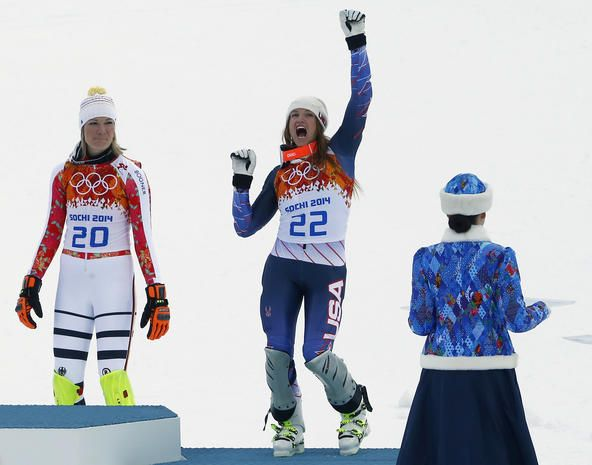 Third-placed Julia Mancuso of the U.S. celebrates on podium in front Germany's winner Maria Hoefl-Riesch (L) during the flower ceremony afte...