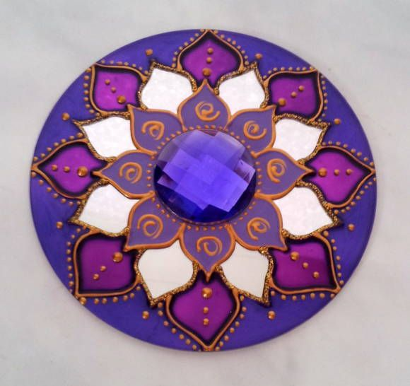 Mandala em CD reciclado, de 12cm de diâmetro, pintura vitral, decorado com pedra acrílica no centro e tinta relevo dourada. Possuí um gancho de metal para ser pendurado na parede. R$ 18,00