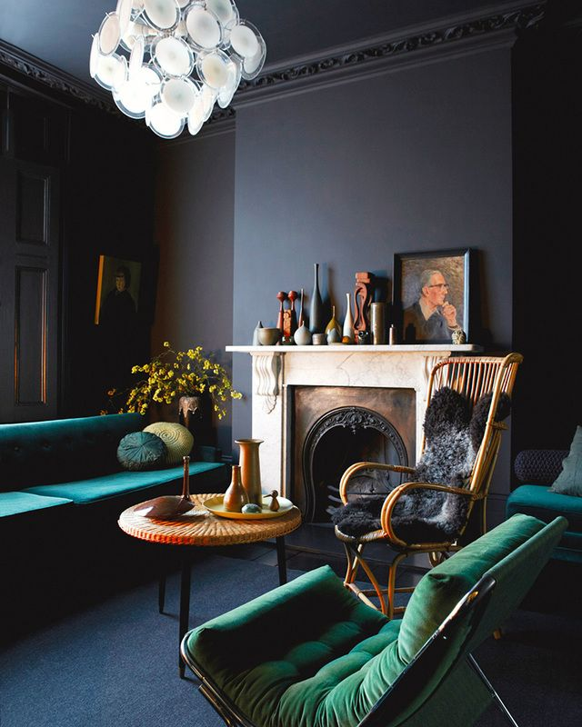 Elegant and dark living room with a green velvet chair and a green couch. The luxurious impression is reinforced by the old chimney. Check out our website to find more velvet inspiration!