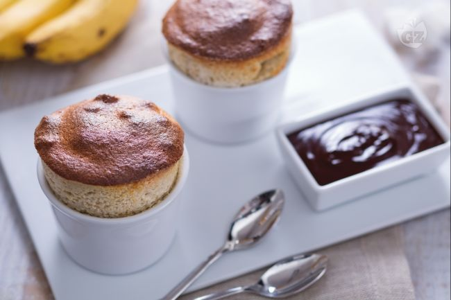 Il soufflé di banane è un morbido e delicato dolce al cucchiaio, servito con una calda crema al cioccolato fondente.