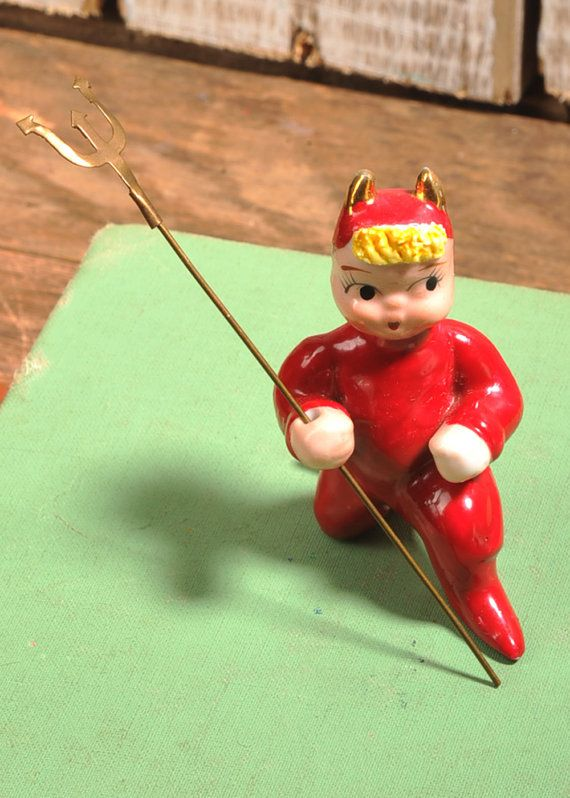 Vintage cute Little red devil, blond, spaghetti porcelain hair. Removable metal pitchfork. Gold accent horns.  No chips, cracks, or repairs. No paint loss. Measures 2 1/2 tall and 2 long. He even still has his sticker on his foot. Made in Japan. He is near mint condition he looks like he lived his whole life in a box.  Take a good look at the images and feel free to ask questions. Shipping overage is always refunded.