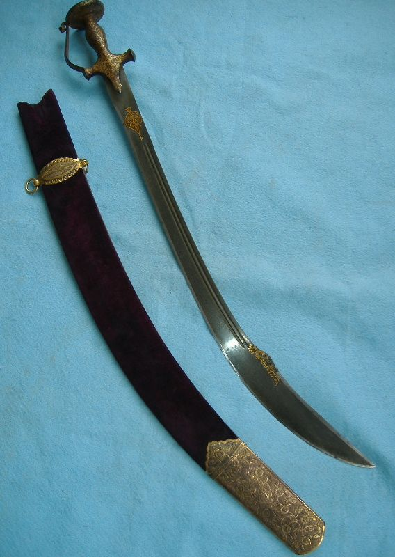 Indian tulwar hilted sword, wootz steel kilij type blade with yelman and gold koftgari hilt, cartouche and inscription. The polish was done by Philip Tom, as was the new scabbard's wooden core. The fittings were done by Thomaz Kaczor in Canada. Overall length(out of scabbard) 31in. / 78.74cm. Length of blade: 27in. / 68.58cm. Ricasso: 1 and 6/8 in. / 4.44cm. Hilt length: 6 1/2 in. / 16.51cm. Disc diameter: 2 1/2 in. / 6.35cm. Length of quillons: 3in. / 7.62cm. Length of langets: 2in…