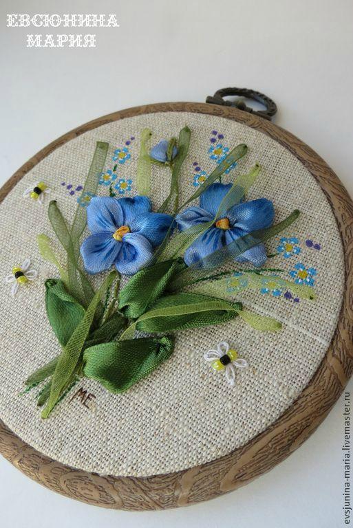Broderie au ruban sur une toile de lin tendue sur un tambour à broder. Des détails sont peints sur les fleurs en ruban et la toile de lin. Des abeilles sont faites de broderie et de perles de rocaille.