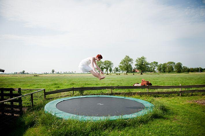 Bruid op trampoline; bruiloft boerderij; trouwen in Friesland