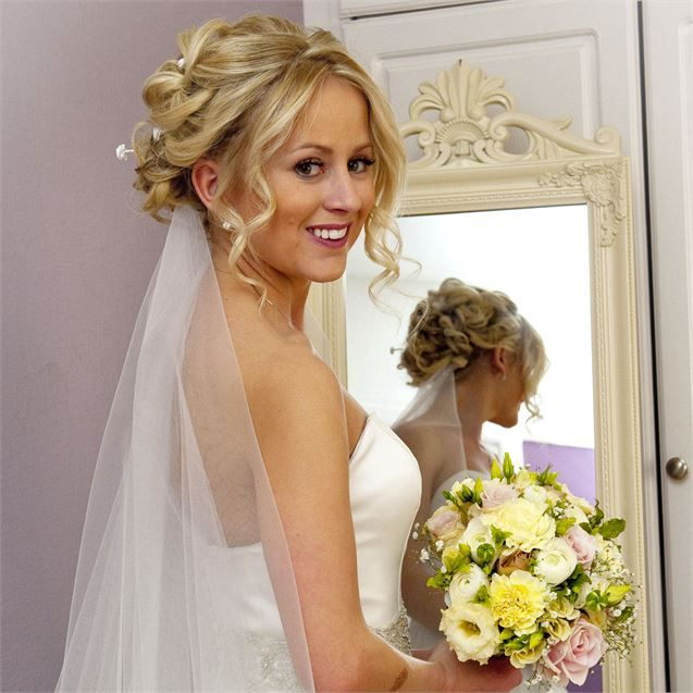 The bride hired a professional hair stylist to create her elaborate wedding hairstyle. She opted for an elegant, curled up do which had lots of tiny i...
