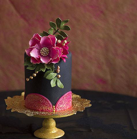 Single-Tier with Pink Flowers: If you're serving several single-tier cakes at your reception, ask your baker to include a bold black confection in the mix. The bright-pink sugar flowers and doily accents balance out the deep, saturated fondant base.