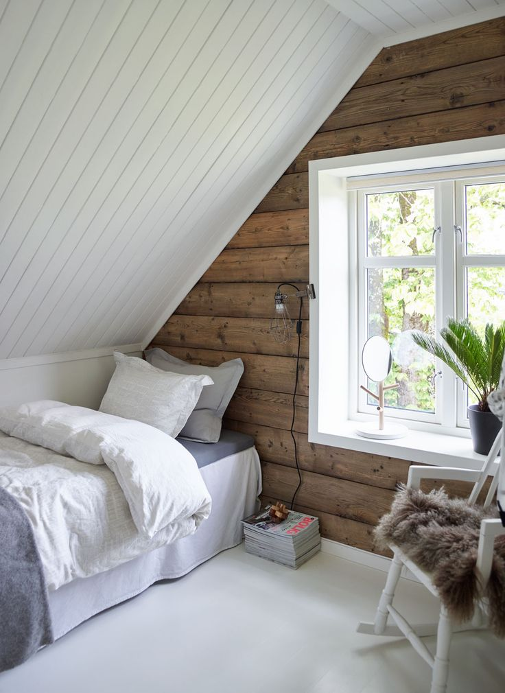 Small attic bedroom-twin bed and rocking chair. Window/street facing wall is ship lap, then wainscotting. Green plants