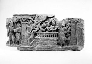 Panel showing the Submission of Apalāla. The haloed Buddha, his body in three-quarter view but with the head almost in profile, stands in a crescentic curve, the overrobe covering both shoulders and the raised neckline evenly curving. He raises one hand with the palm partly inwards, while the other hand secures the robe at waist level. His eyes are open; the hair undulates