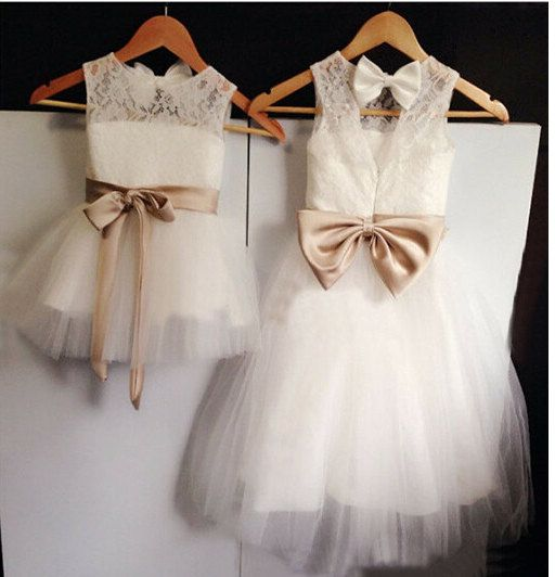 This gorgeous lace dress is accented with a champagne satin sash and 2 bows. The inside is lined with cotton so it is very comfortable for