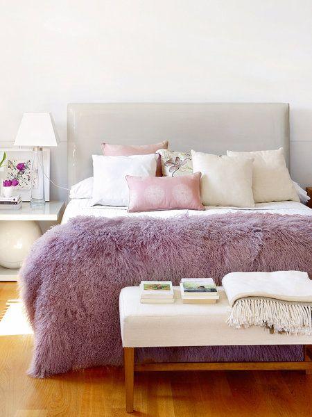 Dormitorio con manta de pelo en color malva a los pies de la cama
