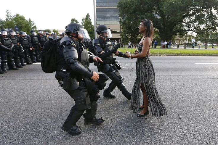 Contemporary Issues, First Prize, Singles—<i>Taking A Stand In Baton Rouge</i>: Lone activist Ieshia Evans stands her ground while offering her hands for arrest as she is charged by riot police during a protest against police brutality outside the Baton Rouge Police Department in Louisiana, USA, on 9 July 2016. Evans, a 28-year-old Pennsylvania nurse and mother of one, traveled to Baton Rouge to protest against the shooting of Alton Sterling. Sterling was a 37-year-old black man and father…