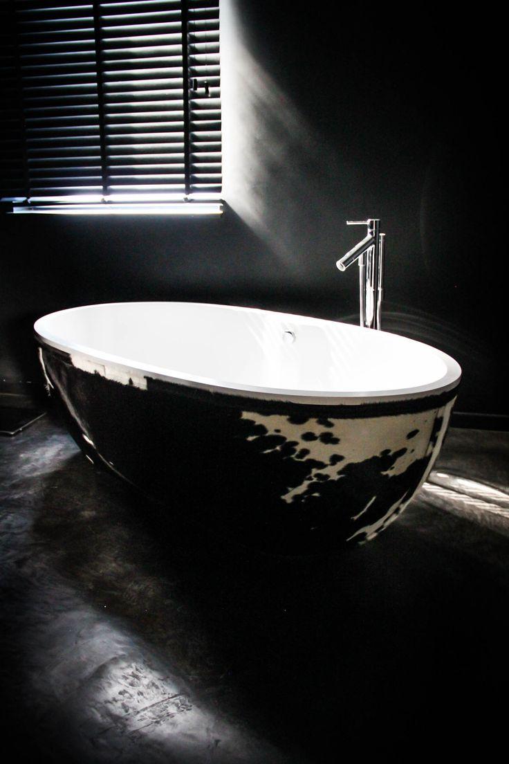 Baignoire recouverte de peau de vache noire et blanche, sol béton lisse noire, murs noirs.