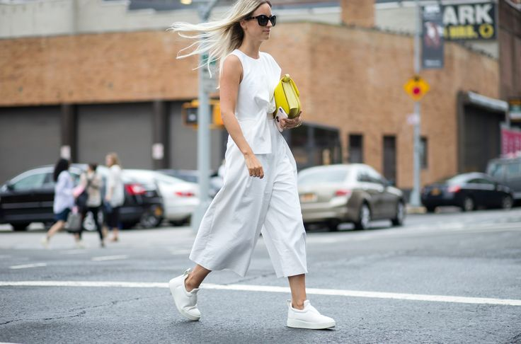 A white Tibi jumpsuit is worn with white Céline sneakers and a yellow bag: