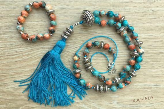 COLLAR: cuentas anudadas manualmente de jade océano azul turquesa, naranja óxido, crema con abalorios plateados y borla decorativa azul. - cuentas: jade océano azul turquesa, naranja óxido, crema (10 mm) - borla: color azul con abalorios plateados (17 cm) Largo total del collar con borla: 58 cm.   PULSERA: cuentas de jade océano azul turquesa, naranja óxido, crema (10 mm) con abalorios plateados