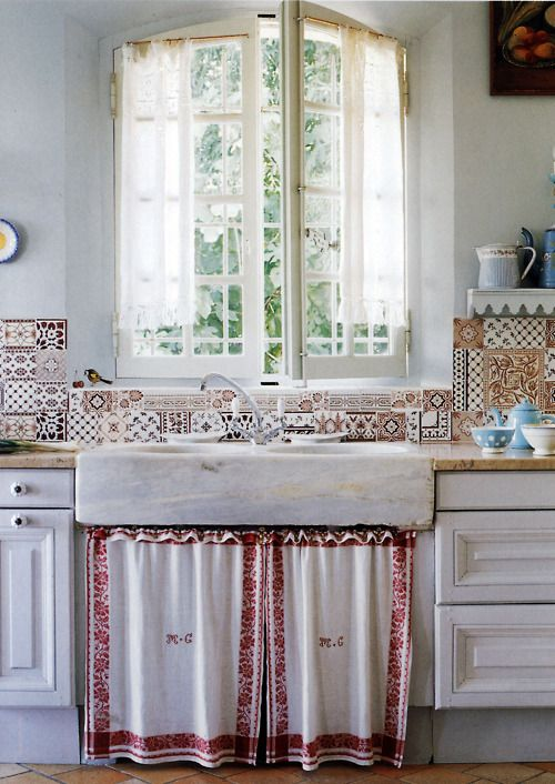 Double marble sink with backsplash and red bordered monogrammed towels (?) to conceal what's beneath.